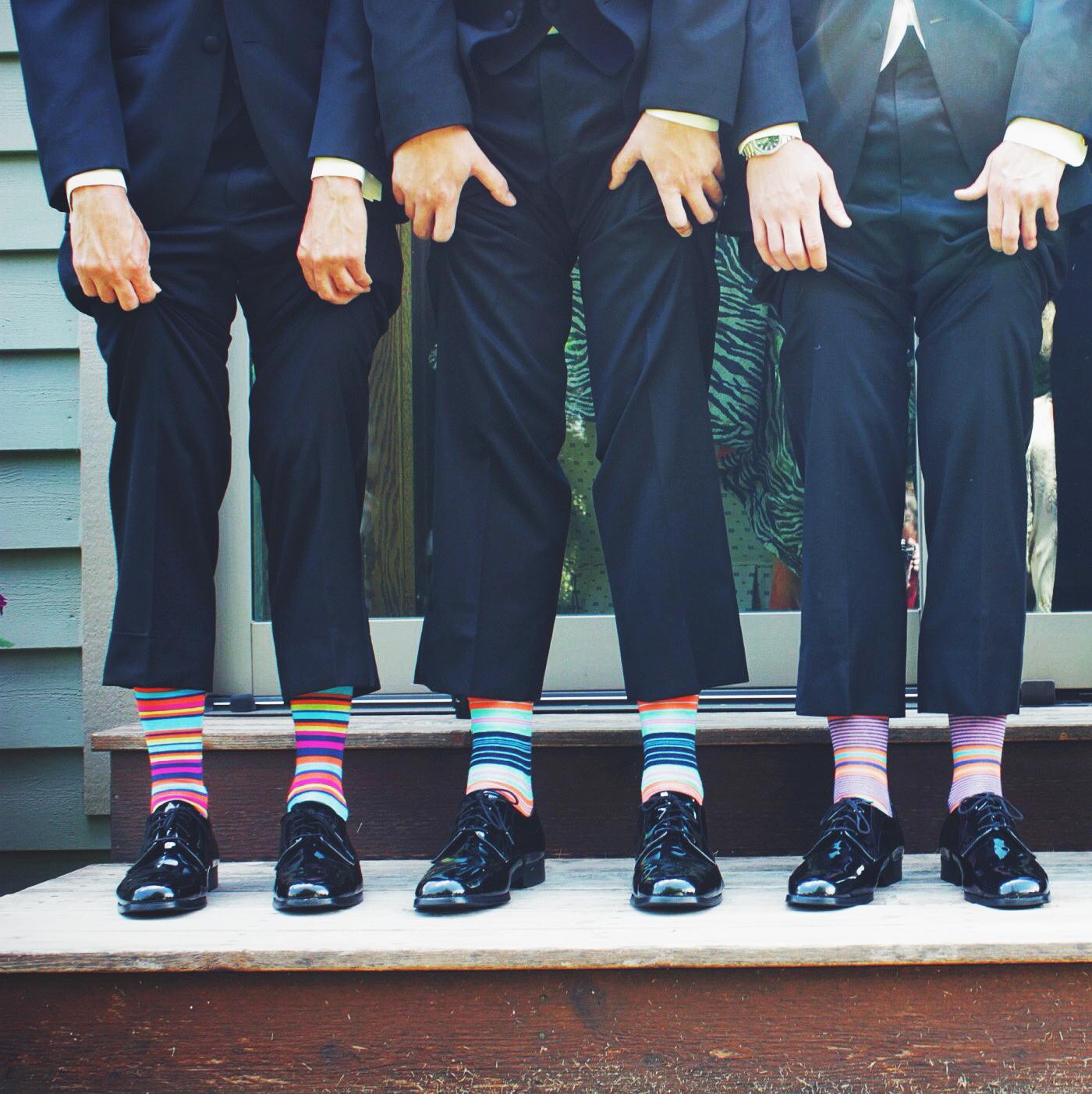 öltönyös úriemberek színes csíkos zokniban